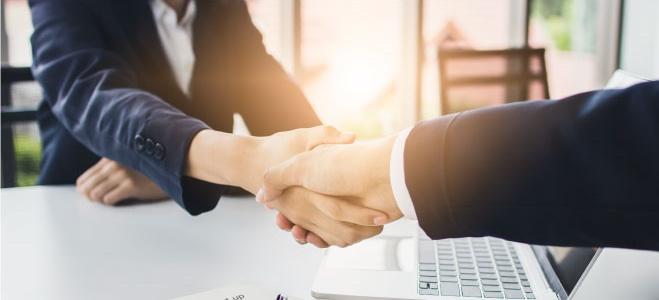 Empresarios llegando a un acuerdo se estrechan las manos